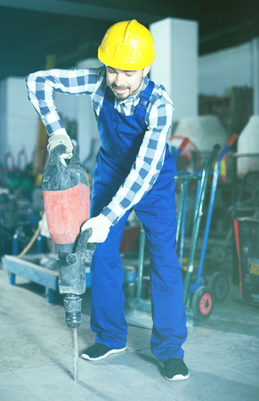 Positive young male worker starting to work with demolition hammer at workshop