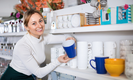Young happy woman choosing new crockery in dinnerware store