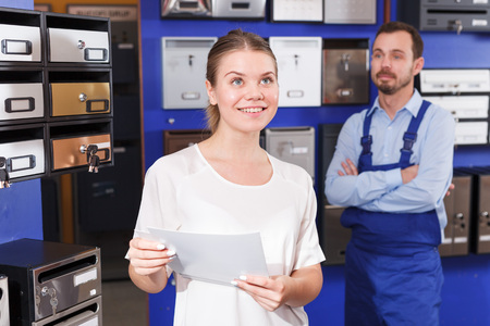 Male worker helping young client woman choosing new mailbox in hardware store