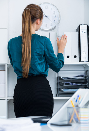 Back view of young businesswoman standing near shelves at office interior