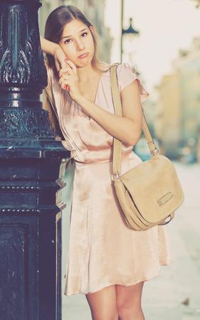 portrait of sad european girl standing outside in city