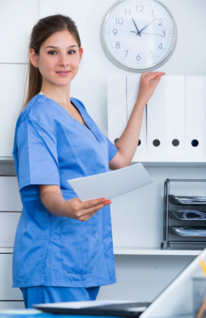 Young female doctor assistant working in office standing near shelves with folders