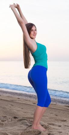 Female is posing on beach in her free time near ocean.