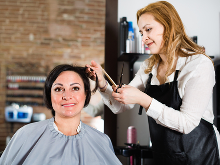 Young positive hairdresser does to woman haircut with use of scissors and hairbrushes in hairdress salon