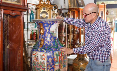 Intelligent Mature Man Pensively Looking At Antique Oriental Stock