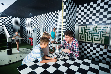 Happy cheerful  family of five is having fun together in lost chessroom.