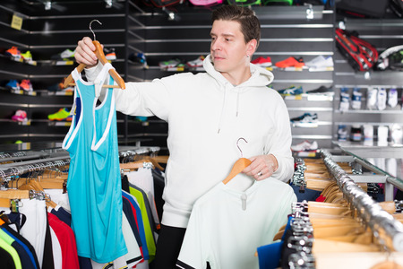 Young male is buying  new T-shirt for tennis in the speciality store.