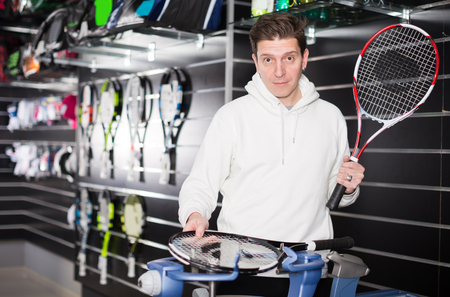 Man master pulls rockets for tennis on the speciality machine indoor. Stock Photo