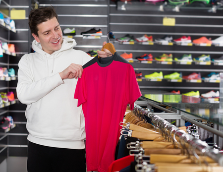 Tennis man is looking on modern shirt for sport in store Фото со стока