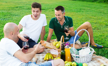 Three men gaily spending time together on picnic on green lawn drinking wine