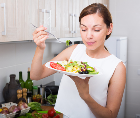 Portrait of smiling young woman eating fresh green salad on kitchen at home