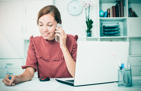 Portrait of young woman talking on phone and looking at computer  screen and write down information in financial documents