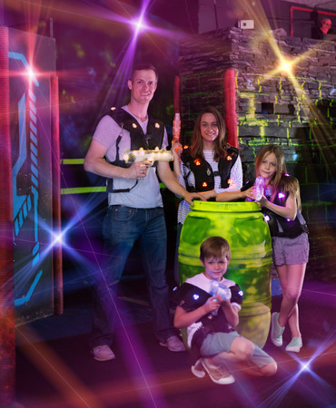 Group of happy kids and adults posing together in colorful beams of laser guns while having fun on dark lasertag arena 免版税图像
