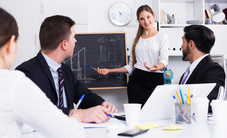Successful smiling business woman presenting new business strategy to partners in office Stock Photo