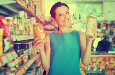 Portrait of woman buying glass jar of  beans in the supermarket