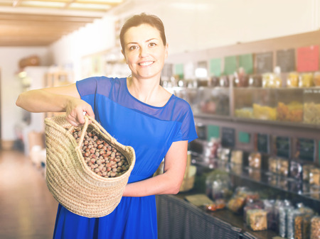 smiling spanish woman displayed big shopping bag with nuts in eco market Stock Photo