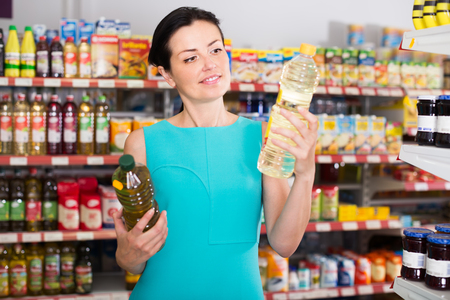 Beautiful female in the supermarket want to buying bottle of oil Stock Photo