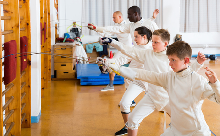 fencers athletes of different ages practicing fencing technique on cushions in gym