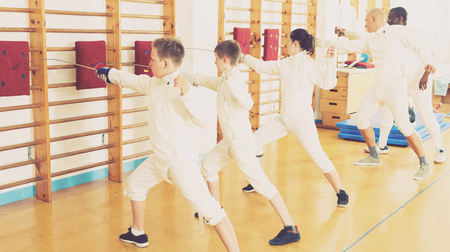 Kids with adults practicing effective techniques of fencing in gym