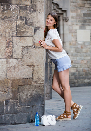 Smiling young woman resting against old stone cathedral wall