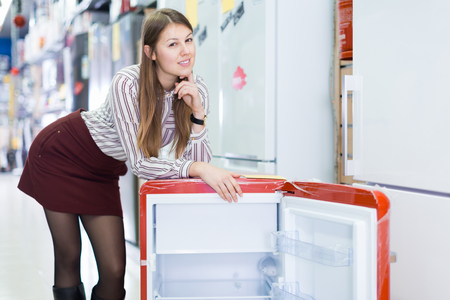 Portrait of young attractive saleswoman in store of house appliances