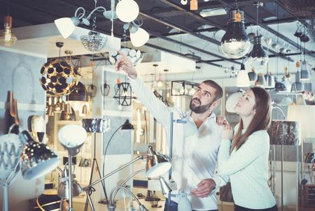 Portrait of couple choosing  suspension lamp in furniture showroom
