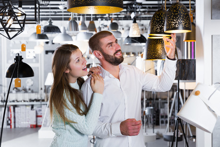 Portrait of smiling family choosing  suspension lamp in furniture showroom