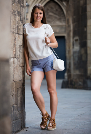 Romantic attractive girl walking on old town streets leaning against stone wall Stock Photo