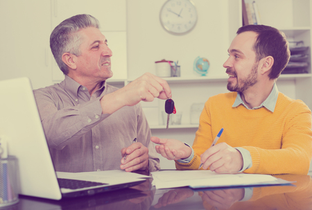 Adult man and young manager sign car purchase contract at office and hand over keys