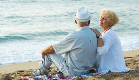 Mature man and woman sitting back on towel at the sea shore