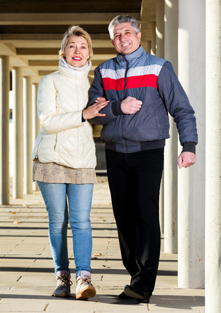 Beautiful married couple goes for walk between concrete pillars on sunny day Stock Photo