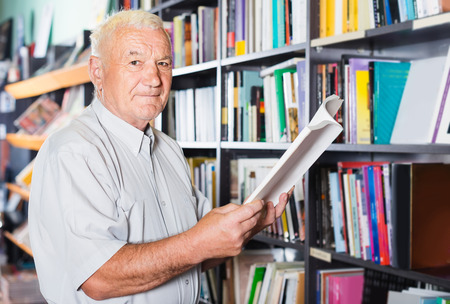 Old positive italian male is choosing book for reading in free time in bookstore. Stockfoto