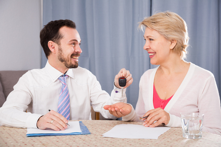 Young manager giving car keys to mature woman according to lease contract