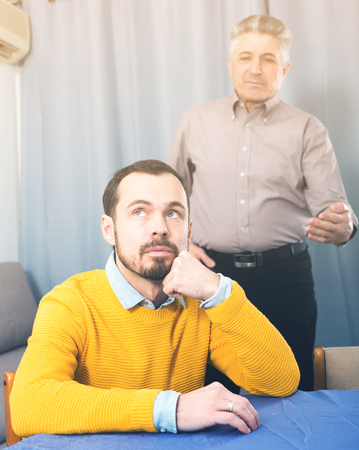 Adult father guides and teaches his son at table at home