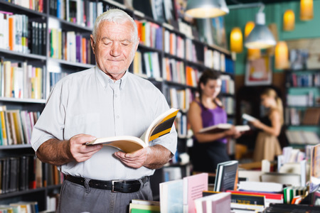 Mature smiling male customer is choosing book for reading in book shop