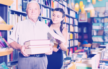 Glad grandfather with granddaughter are choosing books in bookstore