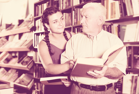 Old man with laughing girl are reading books in bookstore