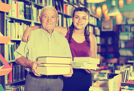 Old man with smiling girl are showing what they bought in bookstore.