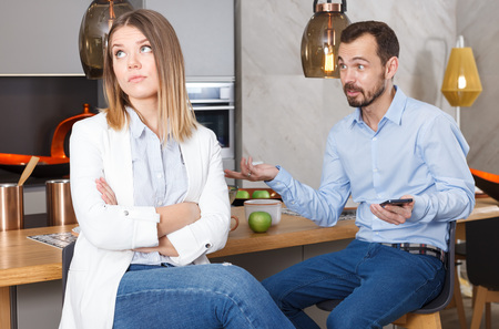 Bored girl sitting at home kitchen table while her boyfriend engrossed in phone Stock Photo