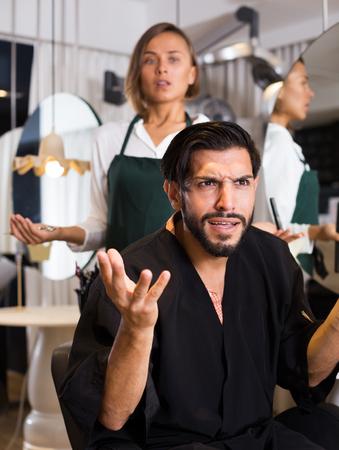 male visitor shocked by thr work female hairdresser in salon