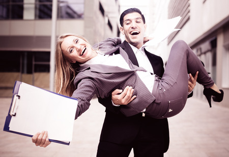Businessman is carry his partner woman on hands because they are signed successful contract outdoors near office. 写真素材