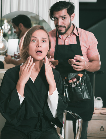 Male professional makeup artist with female visitor shocked Stock Photo
