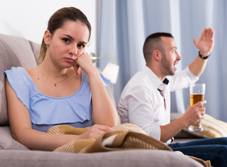 Sad female is sitting alone when her husband is watching TV at home.