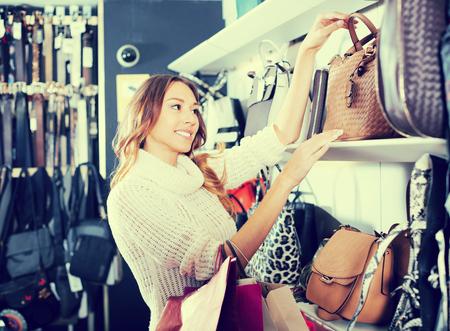 Positive  young woman customer selecting new handbag in shop
