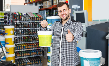 Young smiling man standing near shelves and holding  bucket of paint in household store