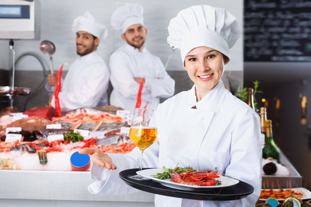 Attractive  cheerful positive female chef with serving tray, offering dishes in fish restaurant Stock Photo