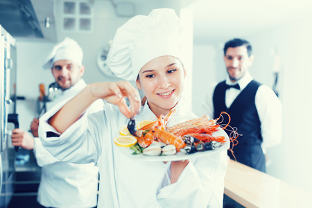 Attractive young woman chef of fish restaurant busy preparing seafood dishes