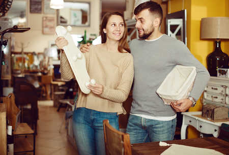Cheerful couple looking for wall hanger in shop of secondhand furniture