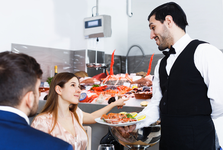 Attractive young girl asking waiter to cook fresh seafood from showcase in fish restaurant