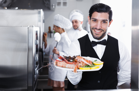 Portrait of handsome waiter with dish of seafood in kitchen on fish restaurant